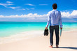 Young man with laptop on the background of turquoise ocean at