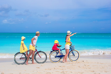 Young family with little kids ride bikes on a tropical exotic