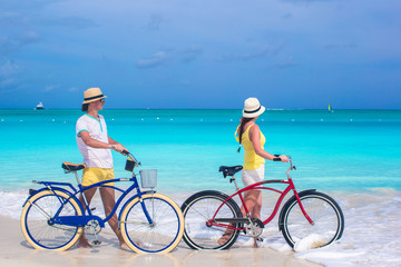 Young couple with bikes on white sandy beach