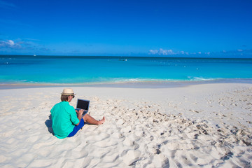 Young man with laptop on background of turquoise ocean