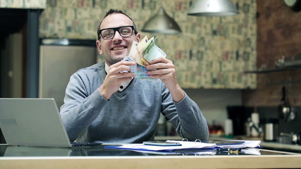 Happy young businessman holding, shaking euro bills, money
