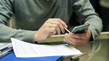 Businessman hands working with smartphone and documents by the d