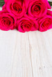 bunch of rose on white wooden surface