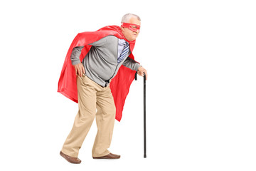 Senior with red cape and mask walking with cane