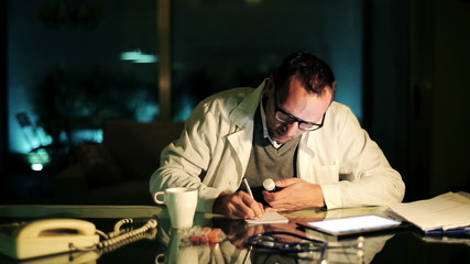 Doctor writing rx prescription at office late at night