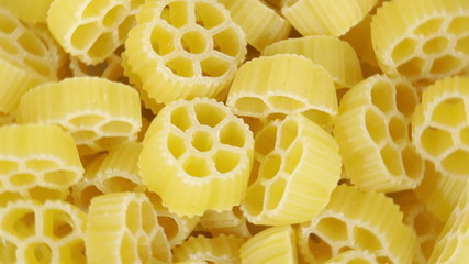 Loopable background of uncooked Italian macaroni pasta.