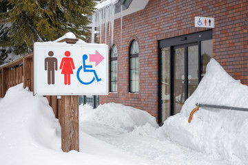 restroom sign in the snow, show the way