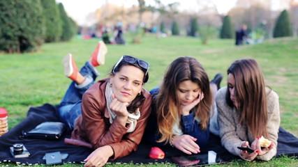 Happy girlfriends relaxing on blanket in the park