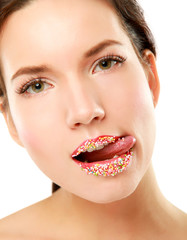close up of woman lips with multicolored pearls