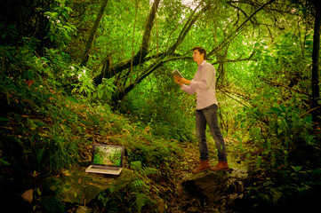 man using tablet with laptop in the forest