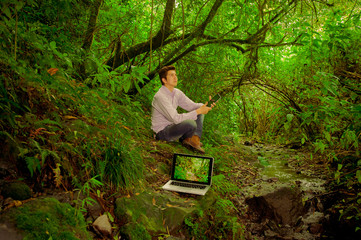 man using tablet and laptop in the jungle