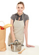 Woman in apron standing near desk with grocery bag