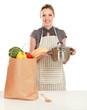 Woman in apron standing near desk with grocery bag ,