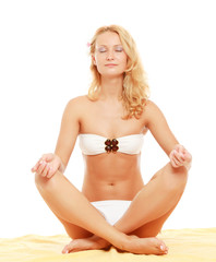 Relaxed young woman in white bikini doing yoga exercise