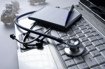 Stethoscope on keyboard and notepad with pen isolated.