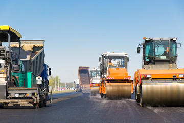 Road rollers, tracked paver and truck during road works