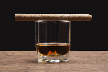 cigar and glass of whiskey on a dark background