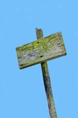 Verwittertes Schild an einem Mast.