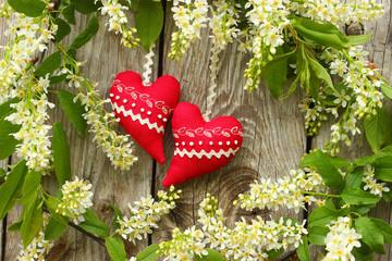 Czerwone serca na drewnianym tle wśród kwiatów