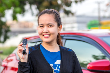 Asian girl showing the car key.