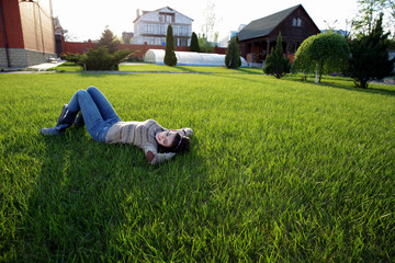 Portrait of a happy woman lying on green grass