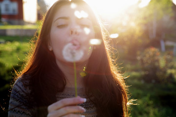 Beautiful woman blowing on dandelion in the garden