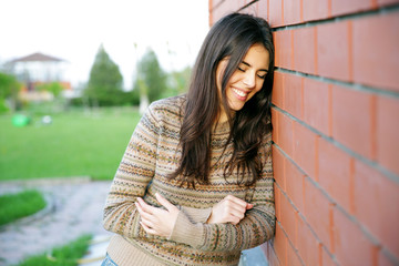 Laughing woman leaning on the brick wall
