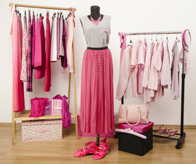 Dressing closet with pink clothes, outfit arranged on mannequin.