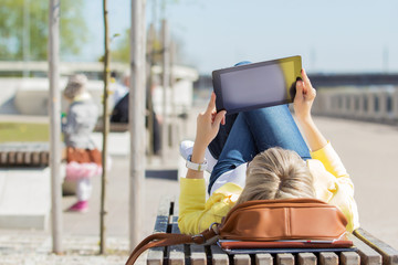 Woman holding digital tablet while laying on bench outdoors