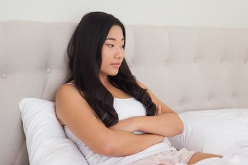Woman sitting in bed with arms crossed