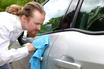 Portrait of funny man washing car with a cloth