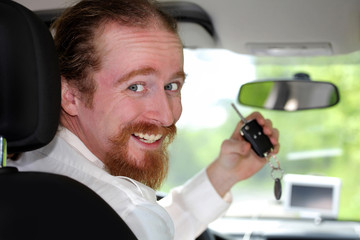 driver smiling sitting in car and showing new car keys