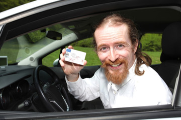 driver smiling sitting in car and showing drivers license