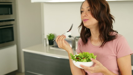 Pretty woman eating a bowl of healthy salad