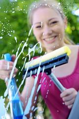 Frau reinigt Auto-Scheibe