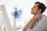 Casual businessman sitting at desk with electric fan