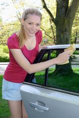 Frau reinigt Auto-Fenster