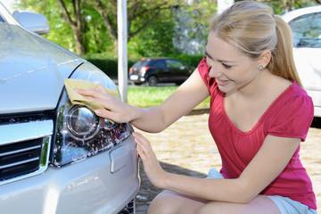 Frau reinigt Auto-Scheinwerfer