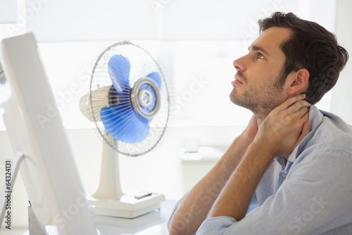 Casual businessman sitting at desk with electric fan - 64324131