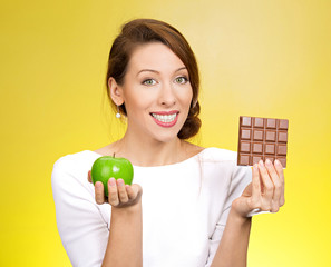Apple over chocolate. Nutritionist on yellow background