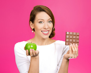 Apple over chocolate. Nutritionist on pink background
