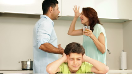 Upset boy covering his ears while his parents fight