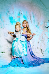 Little girl with mother in princess dress on a background of a w