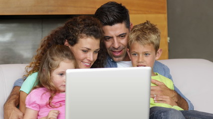 Parents and children using the laptop on the couch