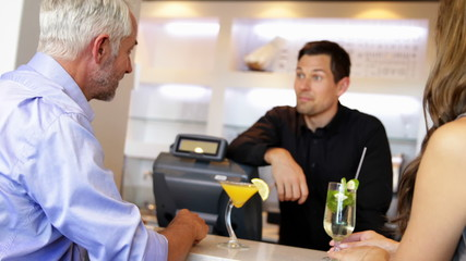 Bartender serving cocktails and chatting to customers
