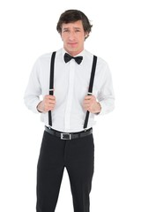 Confident groom holding suspenders