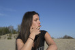 Young sexy female smoking a cigarette at the beach