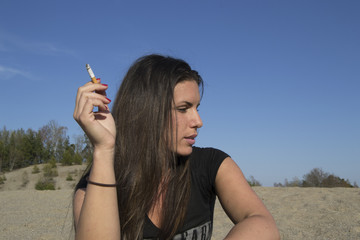 Young sexy woman with a cigarette in her hand (beach)
