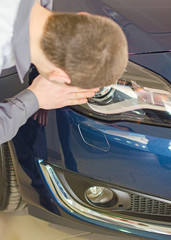 Mechanic wipes car headlight at car service.