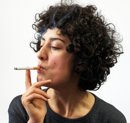 Young woman blows smoke